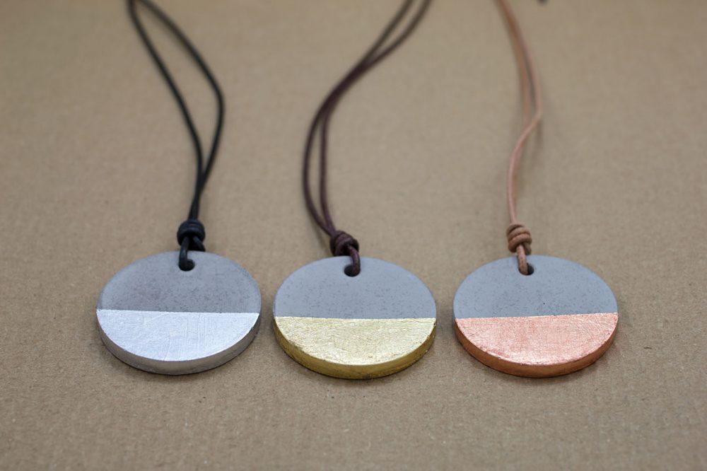runde Anhänger aus Beton mit silberfarbenen, goldfarbenen und rotgoldfarbenen Schlagmetall am Lederband