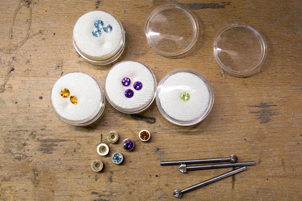 Werktisch mit farbigen Edelsteinen und goldenen Fassungen