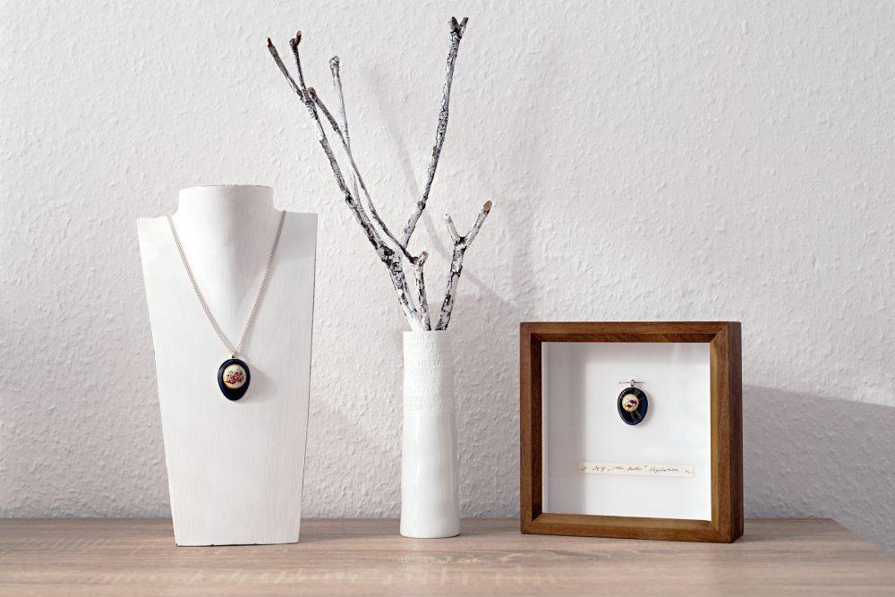 Holzrahmen mit einem Wachteil-Anhänger rechts im Bild, links davon eine Büste mit einem Anhänger und Kette, mittig steht eine Vase mit Zweig